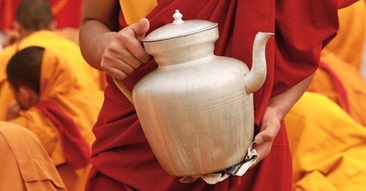 Monaco buddista con in mano una brocca contenente la tisana